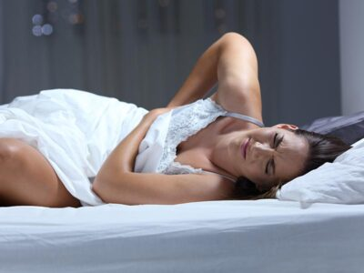 Woman with back pain lying on a mattress