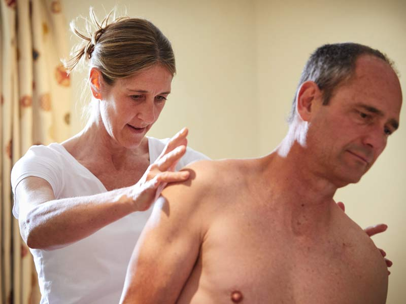 Katie Bench Osteopath Bath area - photo of her examining a client at the Monkton Farleigh Osteopathic Practice
