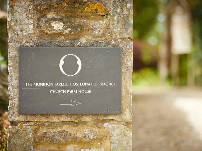 Photo of the sign on the wall of the property for the Monkton Farleigh Osteopathic Practice