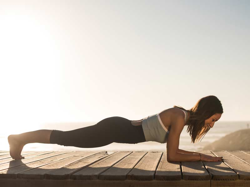Woman doing plank showing good shoulder blade positioning, relevant in osteopathic advice on pilates.