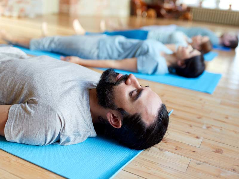4 people lying on mat preparing to centre their pelvis and engage their core muscles. Relevant to osteopathic advice on pilates centring.