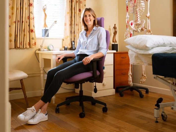 osteopath showing good sitting posture to prevent back pain.